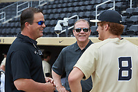 Wake Forest Assistant Athletic Director for Development Bill Merrifield (left) and Athletic Director Ron Wellman (center)chat with pitcher Colin Peluse (8) prior to the game against the Virginia Cavaliers at David F. Couch Ballpark on May 19, 2018 in  Winston-Salem, North Carolina. The Demon Deacons defeated the Cavaliers 18-12. (Brian Westerholt/Four Seam Images)