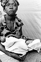 "Guinea. State of ""Guinée Forestière"". Boreah. Camp for Sierra Leoneans refugees. Health center of the non-governmental organization (ngo) Médecins Sans Frontières (MSF) Switzerland. Mother and her new born baby asleep in a white towel. © 2001 Didier Ruef"
