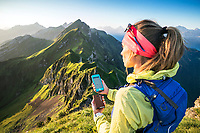 A woman hiker uses an external battery to charge her phone as she uses it for mapping and navigation. Switzerland