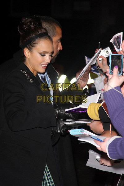 JESSICA ALBA.The 'Valentine's Day' European film premiere at Odeon cinema, Leicester Square, London, England..February 11th, 2010.arrivals half length profile black coat fans crowd signing autographs hair up bun hairband headband head.CAP/AH.©Adam Houghton/Capital Pictures.