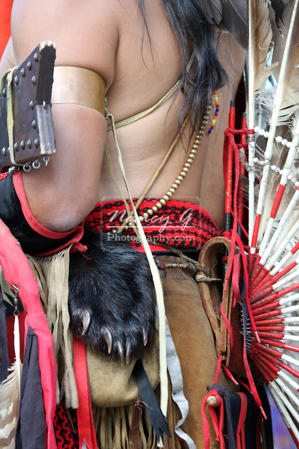 A Native American Indian man with a bear paw ornamentation and feather back display