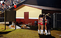 A group of Baker County High School baton twirlers huddle together for warmth on a chilly night before performing at halftime in Macclenny, Fl.