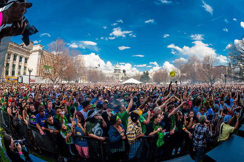 The air is thick with pot smoke as the crowd lights up at 4:20 PM at the 420 Cannabis Culture Music Festival, Civic Center Park, Downtown Denver, Colorado USA. This was the first 4/20 celebration since recreational pot became legal in Colorado January 1, 2014. A crowd of up to 80,000 people attended the event.