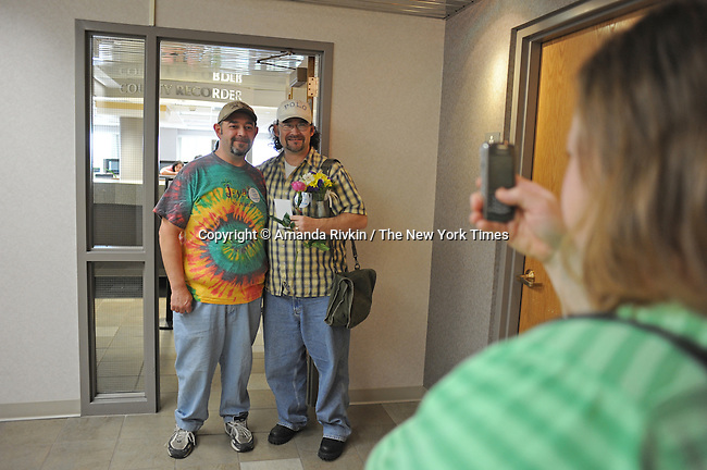 Witness Connie Fuller, 39, takes a picture of Rock Island, Illinois couple (l-r) Curtis Harris, 50, and Daren Adkisson, 39, after they picked up their marriage license first thing in the morning at the Scott County Recorder's Office the first day same sex weddings are legal across Iowa in Davenport, Iowa on April 27, 2009.