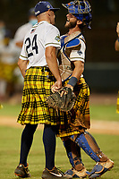 Savannah Bananas pitcher Zachary Cable (24) chest bumps catcher Bill Leroy (1) after closing out a Coastal Plain League game against the Macon Bacon on July 15, 2020 at Grayson Stadium in Savannah, Georgia.  Savannah wore kilts for their St. Patrick's Day in July promotion.  (Mike Janes/Four Seam Images)