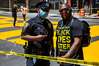 """NEW YORK, NEW YORK - June 14: A policeman poses with a man in the making of the """"Black Lives Matter"""" mural on Fulton St in the Bedford - Stuyvesant neighborhood on June 14, 2020 in Brooklyn, NY. Protesters continue Nationwide after the death of George Floyd. (Photo by Pablo Monsalve/VIEWpress via Getty Images)"""