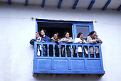 Paucartambo, Peru. Group of nuns on a blue pained balcony looking out from a white painted house.