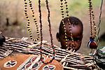Africa, Kenya, Maasai Mara. A young Masai boy peeks from under the makeshift display of handmade jewelry and handicrafts at Olanana in the Maasai Mara.