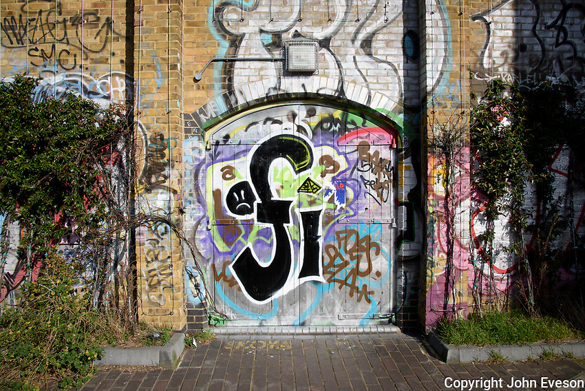 Graffiti on a building at the side of Regents Canal, Bow in Greater London