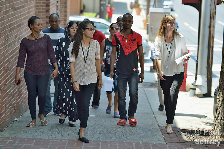 Penny Gushiken (right) walks on a street in Lancaster, Pennsylvania, with members of her cultural orientation class for newly arrived refugees. The class was engaged in a scavenger hunt of sorts, tasked with finding people engaged in specific activities such as eating, listening to music, and taking out trash. The class is sponsored by Church World Service. <br /> <br /> Photo by Paul Jeffrey for Church World Service.