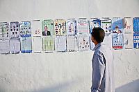 23 ottobre 2011 Tunisi, elezioni libere per l'Assemblea Costituente, le prime della Primavera araba: un uomo osserva i manifesti elettorali dei vari partiti candidati appesi ad un muro nei pressi del seggio.