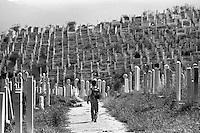 A boy walks through a cemetery on his way to school in the besieged Bosnian capital Sarajevo on September 10, 1994.
