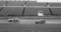 #29 CXamaro of Robert Overby, Chris Doyle, and Don Bell and #85 Porsche 924 of Richard Lloyd, George Drolsom, and Jonathan Palmer race in the rain during the 1983 24 Hours of Daytona , Daytona Internationa Speedway, Daytona Beach, FL, February 1-2, 1983.  (Photo by Brian Cleary / www.bcpix.com)