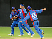 Afghanistan V Ireland - World T20 Qualifying Tournament Final in Dubai Sports City Cricket Stadium - Afghanistan bowler Hamid Hassan is congratulated on a wicket by Samiullah Shenwari (left) and Raees Ahmadzai (right) - Picture by Donald MacLeod 13.02.10
