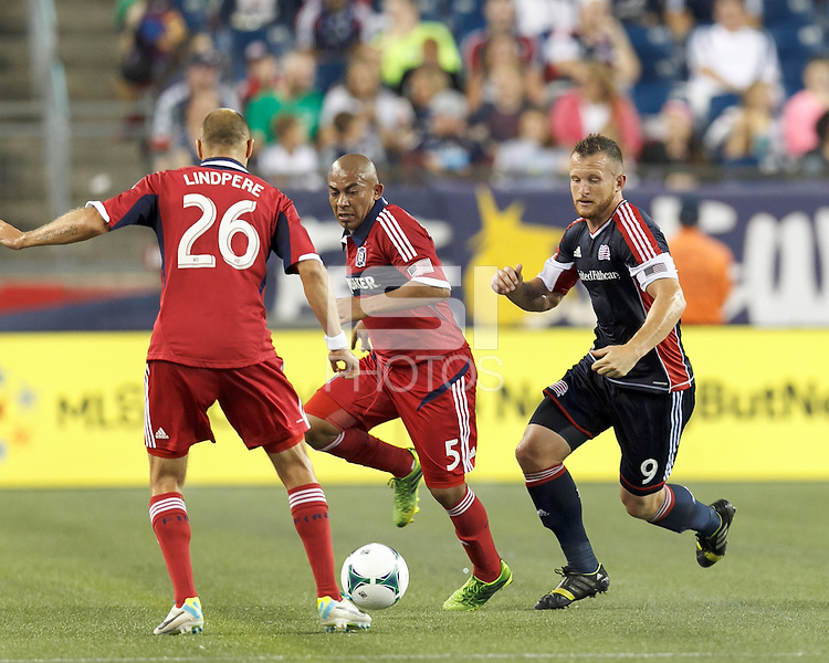 New England Revolution forward Chad Barrett (9) closes on the ball. Chicago Fire midfielder Arevalo Rios (5). In a Major League Soccer (MLS) match, the New England Revolution (blue) defeated Chicago Fire (red), 2-0, at Gillette Stadium on August 17, 2013.