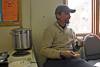 Lance Mackey gets a snack and a coffee during his eight-hour break at Anvik. Photo by Jon Little.