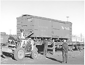 3/4 view of box car #3605 on standard gauge flat car.  Yard tractor/crane is assisting with chore.<br /> D&amp;RGW  Alamosa, CO  Taken by Richardson, Robert W. - 12/14/1955