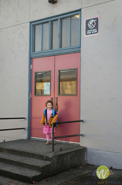 Pre-school toddler at school entrance with weapons free zone sign.