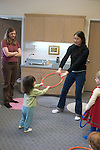 Berkeley CA Asian teacher working with rings and dance rhythms in family music program for toddlers