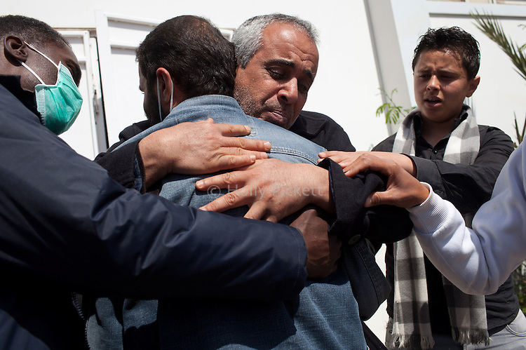 A man was comforted outside of the hospital morgue in Benghazi, Libya, March 20, 2011. Family members prepared those killed during fighting between opposition rebels and loyalist forces of Col. Muammar Qaddafi for burial. The main hospital in Benghazi reported around 50 dead fighters and civilians the previous day and at least 35 on Sunday.