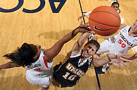 Dec. 18, 2010; Charlottesville, VA, USA; UMBC Retrievers 6-0 Meghan Colabella forward (10) shoots the ball between Virginia Cavaliers guard Paulisha Kellum (3) and Virginia Cavaliers forward Chelsea Shine (50) during the game at the John Paul Jones Arena. Virginia won 61-46. Mandatory Credit: Andrew Shurtleff
