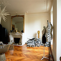 Graphic patterns, added to a simple palette of white, black and gold create an elegant combination, whilst the contemporary furniture contrasts with the original period features in this Paris apartment. Three Stockman mannequins designed by artist Emmanuel Bossuet stand to one side of the room