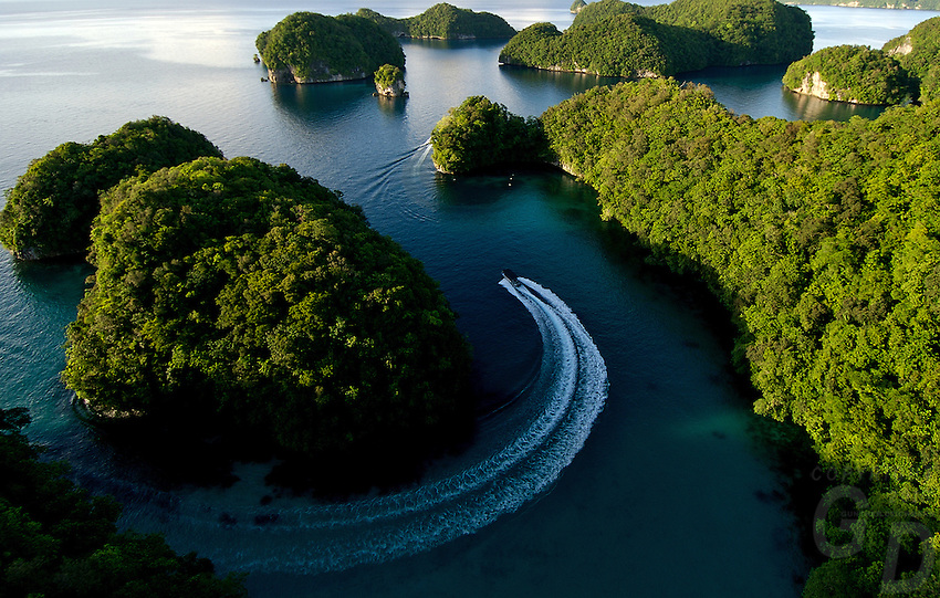 Aerial view of the Rock Islands in the late afternoon Natural Arch area,a dive boat returning from a dive trip Palau, <br /> Micronesia