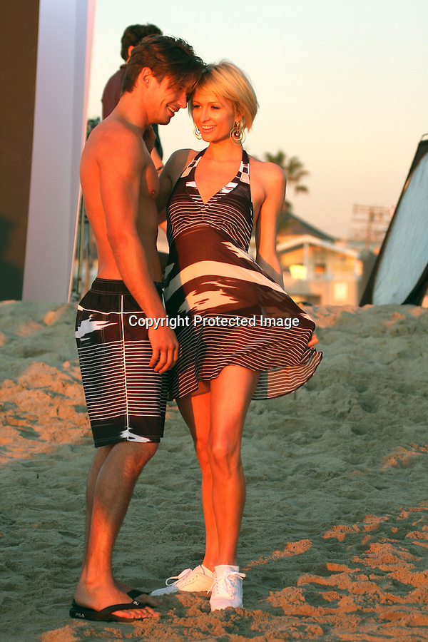 1-19-09.Paris Hilton on a photo shoot for Fila Clothing in Venice Beach California. She did about 5 wardrobe changes. Not sure who the male model is.  When paris was walking back to her trailer a roller skater almost knocked her over. Luckily her body guard pulled her to safety. ...www.AbilityFilms.com.805-427-3519.AbilityFilms@yahoo.com