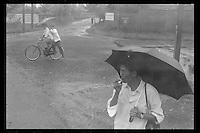 A Chinese man smokes a cigarette at a bus stop as others pass by on a bicycle in Jiangdu, Jiangsu province, China, 1983.