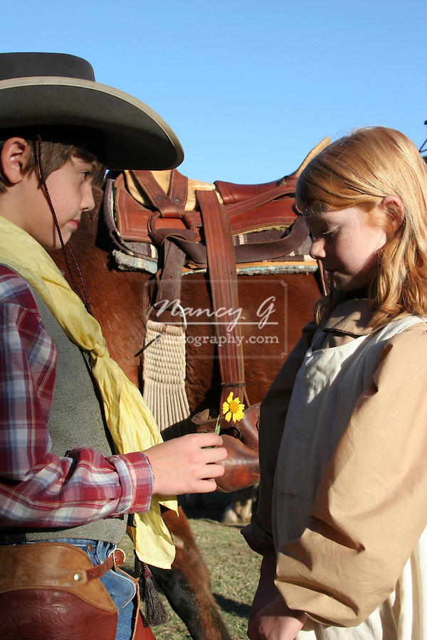 A young cowboy giving a flower to a young girl in the old west