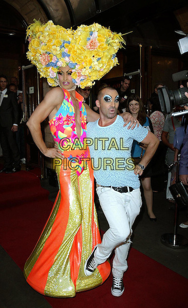 "CAST MEMBER & LOUIE SPENCE.""Priscilla: Queen Of The Desert The Musical"" - Cast Change, London, England, UK..June 22nd, 2010.arrivals full length make-up grey gray t-shirt white trousers trainers converse leopard blue animal print drag queen costume hat character funny yellow flowers.CAP/WIZ.© Wizard/Capital Pictures."