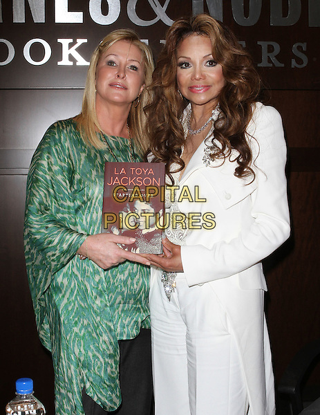 Kathy Hilton, La Toya Jackson.book signing for 'Starting Over' held at Barnes & Noble at The Grove, Los Angeles, California, USA 28th June 2011.half length white jacket trousers green animal print leopard diamond necklace holding book.CAP/ADM/KB.©Kevan Brooks/AdMedia/Capital Pictures.