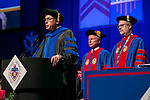 Ray Whittington, dean of the Driehaus College of Business, introduces the honorary degree recipient, Rick Kash, center, vice chairman of the global consumer information analytics firm Nielsen, before he receives his honorary degree Sunday, June 11, 2017, during the DePaul University Driehaus College of Business commencement ceremony at the Allstate Arena in Rosemont, IL. (DePaul University/Jamie Moncrief)