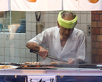 A cook in a yakitoriya, a bar serving fried pieces of chicken or meat on skewers.