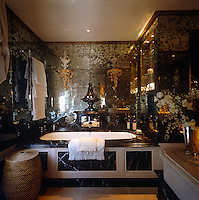 The walls of this dramatic dark marble bathroom are covered in antique mirrored panels