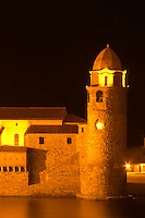 The church Eglise Notre Dame des Anges, our lady of the angels. With its emblematic church tower. Collioure. Roussillon. France. Europe. In the evening with illumination and street lights.