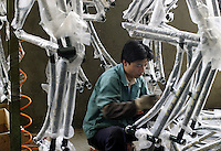 A worker adds componets to bicycle frames at the Shanghai Forever Bicycle Factory (SFBF) in Shanghai, China. Despite the government's efforts to encourage automobile ownership in recent years, the bicycle remains the most popular mode of transportation for China's masses. The SFBF, it's products once a must have and a symbol of status for every Chinese family, are now supplying bicycles to countries around the world. It has seen it's sales increase 59% percent in the past year to 876 million yuan (euro 89.36 million)..21-APR-04