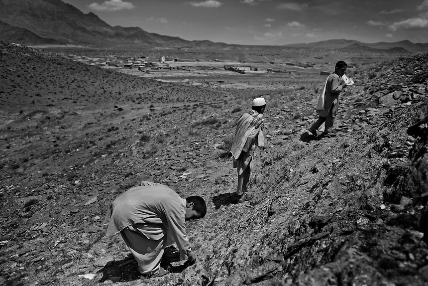 KHAK-E-JABAR DISTRICT, AFGHANISTAN - MAY 15. .(from left) 12-year-old Safiullah, 10-year-old Sayedullah and 8-year-old Zahedullah look for scrap metal and shrapnel from exploded anti-personel mines outside their village in Khak-e-Jabar district. The areas in and around the capital Kabul were heavily mined during the Soviet invasion of Afghanistan during the 1980's. (Javier Manzano / For The Washington Post). ..