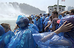 Niagara Falls, Ontario, Canada - 01 August 2006---Tourists / visitors  equipped with blue plastic coats against the mist cruising on the Niagara River, with the American Falls on the United States' side (le)--- people, tourism, transport---Photo: © HorstWagner.eu