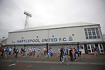 Supporters of Hartlepool United and Middlesbrough making their way past the main entrance at the Victoria Ground, Hartlepool, after the pre-season friendly between the two teams. Hartlepool were relegated to League Two at the end of the 2012-13 season whilst their Teesside neighbours remained two divisions above them in the Championship. The game ended in a no-score draw, the home team's goalkeeper Scott Flinders saving a second-half penalty from Boro's Lucas Jutkiewicz, watched by a crowd of 2307.