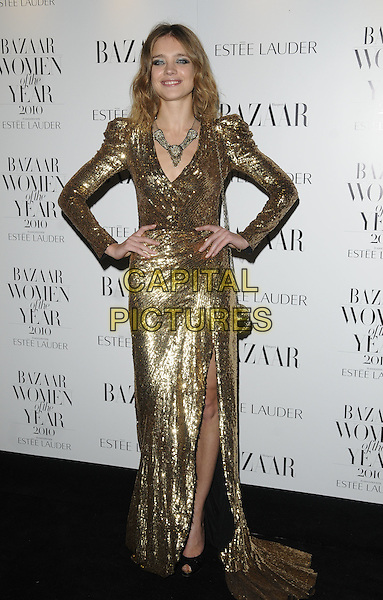 NATALIA VODIANOVA.Harper's Bazaar Women of the Year Awards at One Mayfair, London, England, UK. .November 1st 2010.full length gold dress sequined sequin maxi long sleeve necklace slit split hands on hips.CAP/CAN.©Can Nguyen/Capital Pictures.