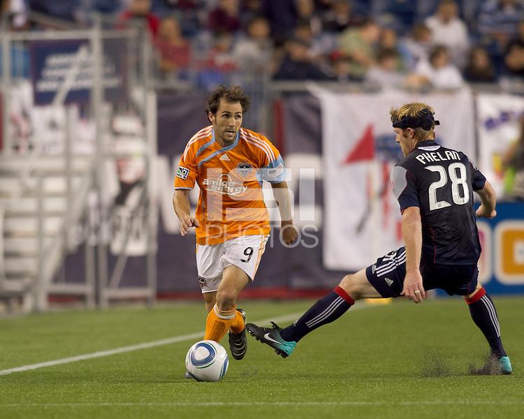 Houston Dynamo midfielder Brian Mullan (9) dribbles as New England Revolution defender Pat Phelan (28) defends. The New England Revolution defeated Houston Dynamo, 1-0, at Gillette Stadium on August 14, 2010.