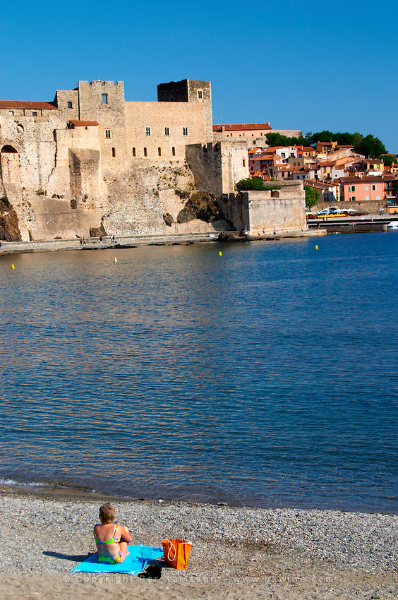 A lone woman on the beach on a towel. The beach in the village. The chateau in Collioure harbour. Collioure. Roussillon. France. Europe.