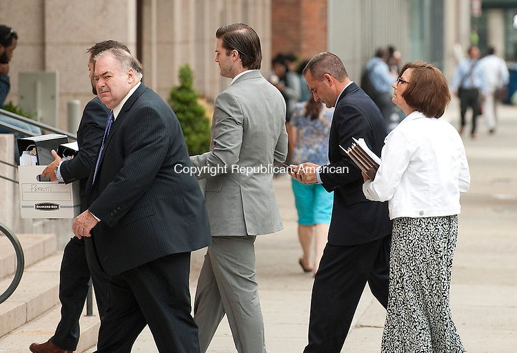 NEW HAVEN, CT--- -070915JS01-- Former Middlebury fire chief Paul J. Perrotti, second from right,  makes his way into the U. S. District Courthouse in New Haven on Thursday. Perorotti is accused of embezzling over $70,000 for the department, the town and FEMA to benefit his private electrical business. <br /> Jim Shannon Republican-American