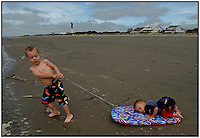Two young boys, brothers, play with one another during a family vacation to the beach near Charleston, SC. Model released image may be used to illustrate other destinations or concepts.