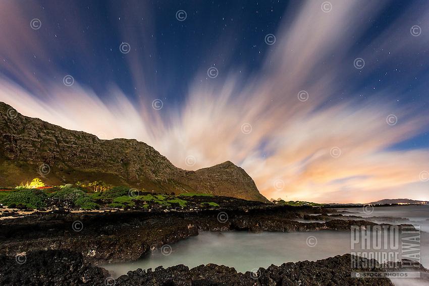 A view of tidal pools backed by the Ko'olau mountains under a starry night sky streaked with clouds, Makapu'u Beach, Waimanalo, O'ahu.