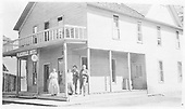 3/4 view of the Placerville Hotel with four people posing for the photographer.<br /> Placerville, CO