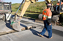 A worker looks on as an excavator pulls dirt from a trench and loads it into a truck. The cities of Palo Alto and Mountain View are jointly constructing a reclaimed water pipeline to carry recycled water from the Palo Alto Regional Water Quality Control Plant to customers along East Bayshore Parkway and Mountain View's North Bayshore area.