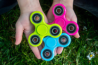 A young boy holds a green blue and pink fidget spinner