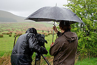 Film cameraman and director,  holding umbrella, filming in the rain, Whitewell, Lancashire, England. Camera has wet weather protective cover.....Copyright..John Eveson,.Dinkling Green Farm,.Whitewell,.Clitheroe,.Lancashire..BB7 3BN.Tel. 01995 61280.Mobile 07973 482705.j.r.eveson@btinternet.com.www.johneveson.com